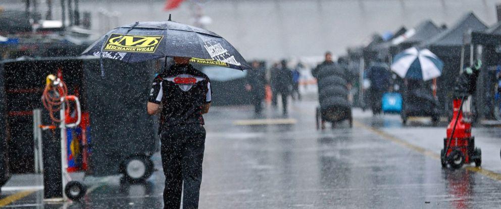 A man walks through the pit area as rain falls before a NASCAR Cup Series auto race, Saturday, Aug. 18, 2018, in Bristol, Tenn.