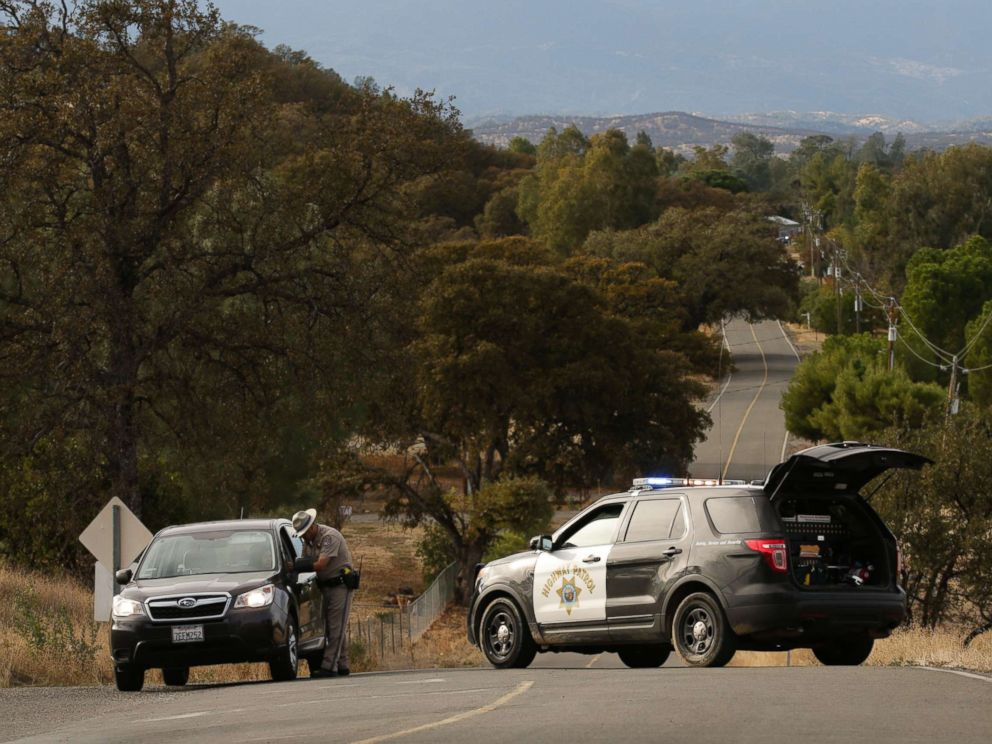 PHOTO: A Highway Patrol officer speaks to a woman while blocking off a road to traffic after a shooting on Nov. 14, 2017, in Rancho Tehama, Calif.