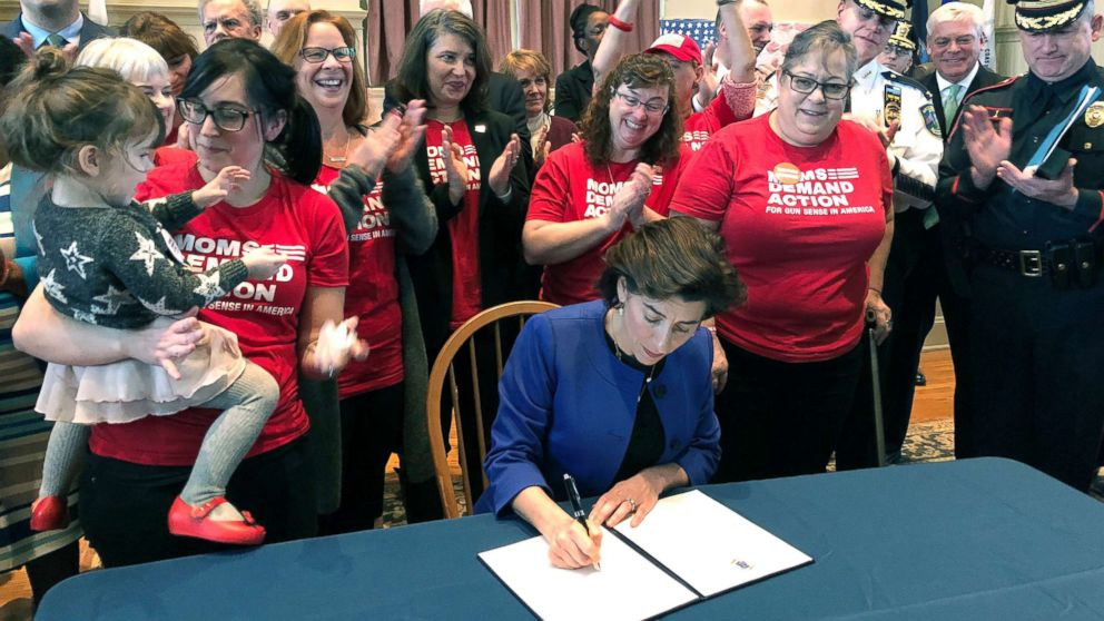 Cheers erupt as Rhode Island Gov. Gina Raimondo signs an executive order, Feb. 26, 2018, in Warwick, R.I., to establish a new policy to try to keep guns away from people who show warning signs of violence.