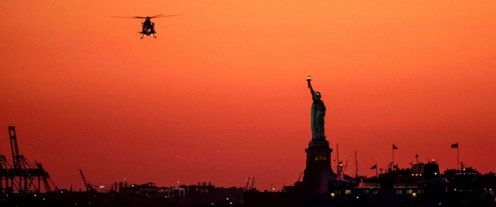 PHOTO: A helicopter flies past the Statue of Liberty as the sun sets on Oct. 14, 2019 in New York City.