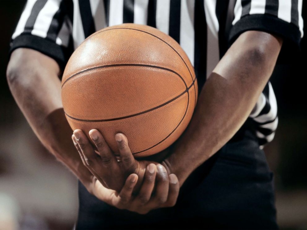 PHOTO: A referee holds a basketball.