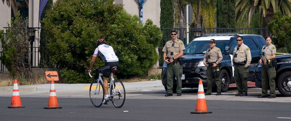 PHOTO: A cyclist rides past several San Diego County Sheriffs who are standing in front of the Chabad of Poway synagogue in Poway, Calif., April 28, 2019.