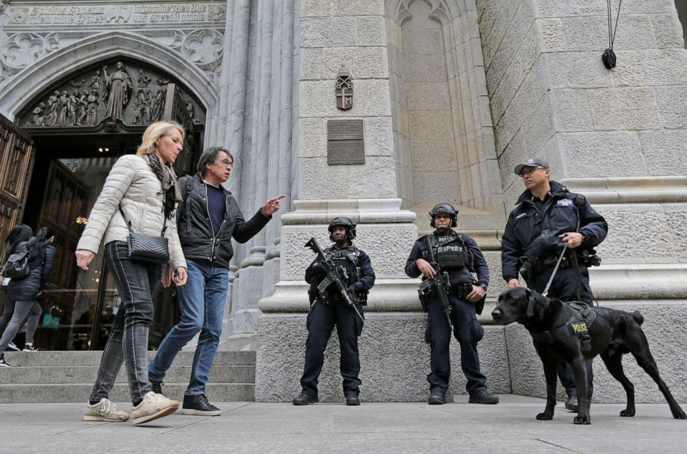 PHOTO: Tourists walk past police officers standing in front of St. Patricks Cathedral in New York, April 18, 2019.