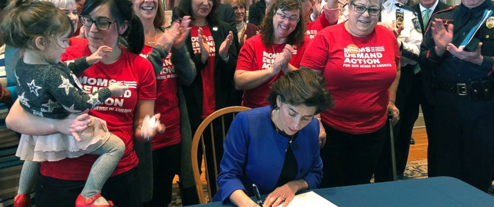 Cheers erupt as Gov. Gina Raimondo signs an executive order Monday in Providence, R.I., to establish a new policy allowing relatives or police to ask judges to temporarily strip gun rights from people who show warning signs of violence.