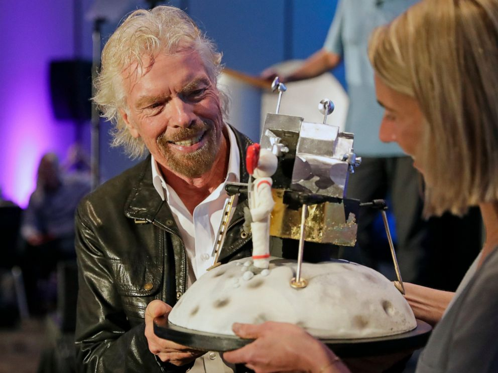 PHOTO: Richard Branson is presented with a space-themed cake during a lunch attended by Virgin Galactic ticket holders, to mark his 69th birthday and in recognition of the Apollo 11 moon landing anniversary Thursday, July 18, 2019, in Cape Canaveral, Fla.