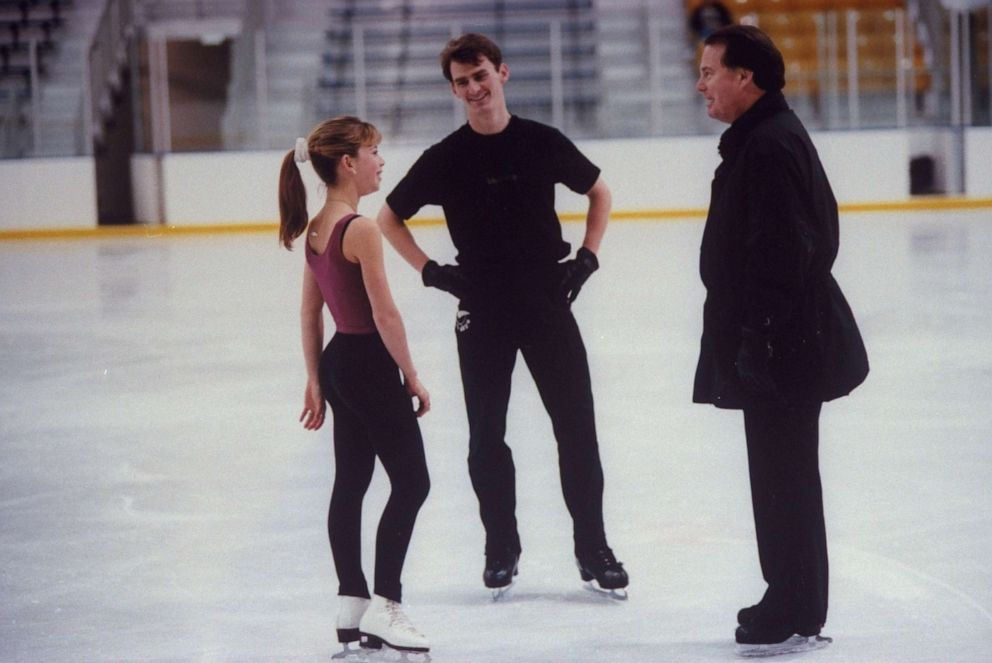 PHOTO: In this file photo from 1997, figure skating champion Todd Eldredge (C) chats with figure skating champion Tara Lipinski & his coach Richard Callaghan during a break in practice session at the Detroit Skating Club.