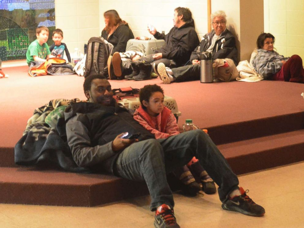 PHOTO: Abdulai Salam and his daughter Mina wait for the all-clear at Homer High School during a tsunami alert for Homer, Alaska at about 2:30 a.m., Jan. 23, 2018.