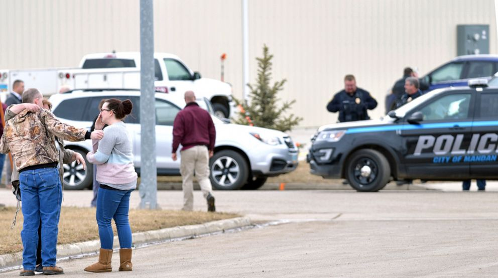 PHOTO: Family and friends console each other at the scene near the south side of the RJR Maintenance and Management building in Mandan, N.D., April 1, 2019.