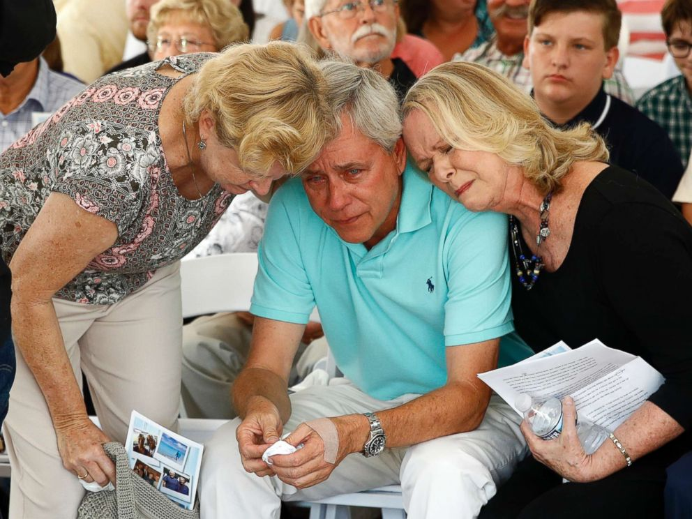PHOTO: Carl Hiaasen, center, brother of Rob Hiaasen, is consoled by his sister Judy, right, during a memorial service, July 2, 2018, in Owings Mills, Md.