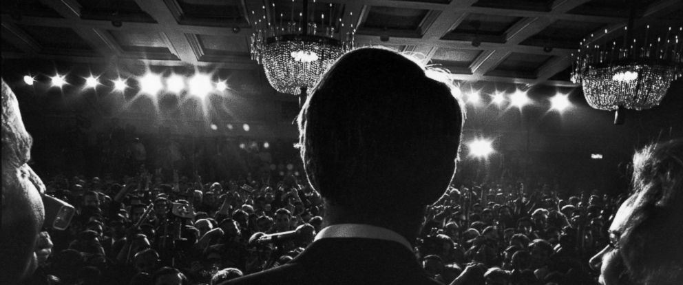 PHOTO: Rear view of Sen. Robert Kennedy and his pregnant wife Ethel standing at a podium at the Ambassador Hotel as he addresses supporters after his California primary election victory, Los Angeles, June 5, 1968.