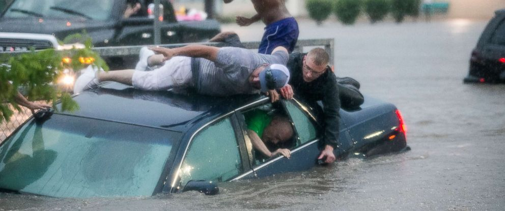 People work to rescue a person was trapped in floodwaters on Monday, June 18, 2018, in the parking lot of the Schnucks on East Charles street in Rockford, Ill.