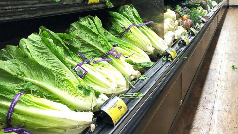 In this Nov. 20, 2018, file photo, romaine lettuce sits on the shelves as a shopper walks through the produce area of an Albertsons market in Simi Valley, Calif.