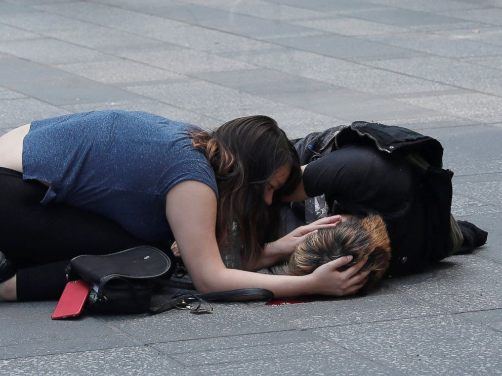 PHOTO: A woman attends to an injured man on the sidewalk in Times Square after a speeding vehicle struck pedestrians on the sidewalk in New York City, May 18, 2017.