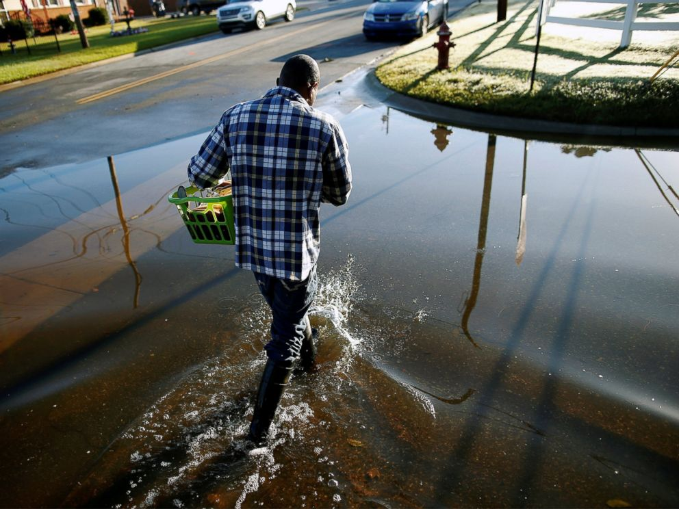 PHOTO: Marquis Sheffield of Herbert Street retrieves clothing from his flooded home after Hurricane Matthew caused severe flooding in Goldsboro, North Carolina, Oct. 13, 2016.