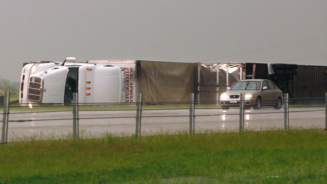 PHOTO: A car passes two semi tractor-trailers, flipped by a tornado, along I-40 eastbound just east of El Reno, Okla., May 31, 2013.
