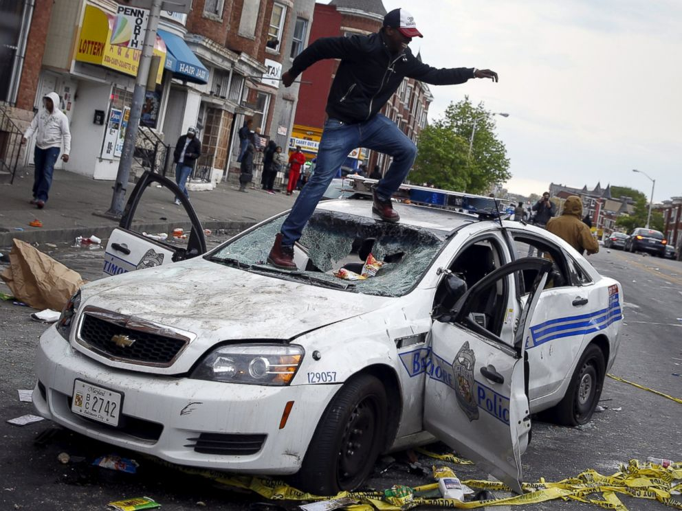 PHOTO: Demonstrators jump on a damaged Baltimore police department vehicle during clashes in Baltimore, Md., April 27, 2015.