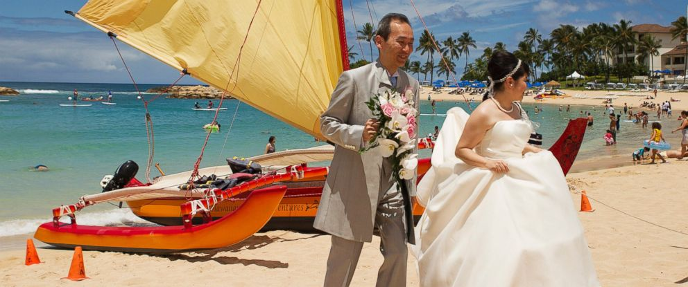 PHOTO: A Japanese couple walks past a sailing canoe on the beach after taking wedding pictures as two hurricanes approach the Hawaiian islands, in Honolulu, Hawaii, August 6, 2014.
