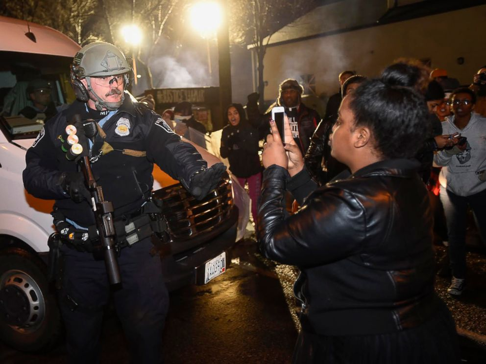 PHOTO: A police officer tells a women to back up as she photographs him in front of a north Minneapolis police precinct during a protest in response to Sundays shooting death of Jamar Clark by police officers in Minneapolis, Nov. 18, 2015.
