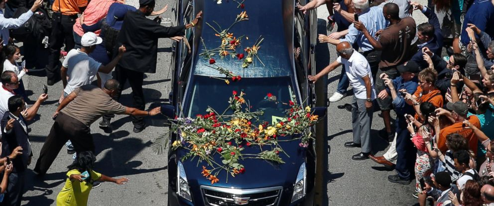PHOTO: Well-wishers touch the hearse carrying the body of the late boxing champion Muhammad Ali during his funeral procession through Louisville, Kentucky, June 10, 2016.