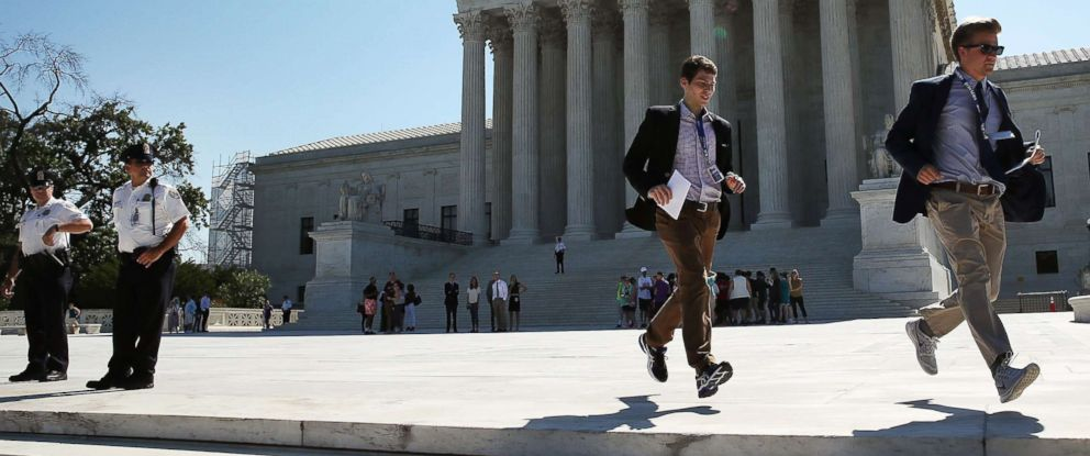 PHOTO: Two CBS interns run with a newly released Supreme Court ruling June 20, 2016 in Washington.