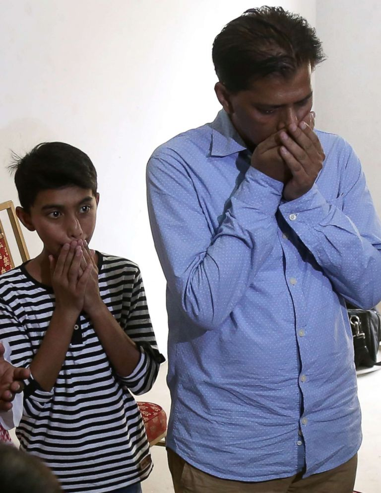 PHOTO: Abdul Aziz Sheikh, the father of Sabika Sheikh, with his son Ali, mourn the loss of his daughter, May 19, 2018. Sheikh was an exchange student from Pakistan and was one of the ten students killed in the school shooting in Santa Fe, Texas.