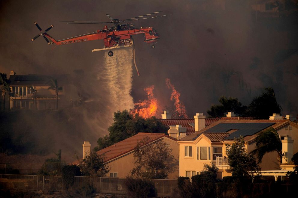 PHOTO: A helicopter drops water while battling a wildfire called the Saddle Ridge Fire in Porter Ranch, Calif. on Oct. 11, 2019.