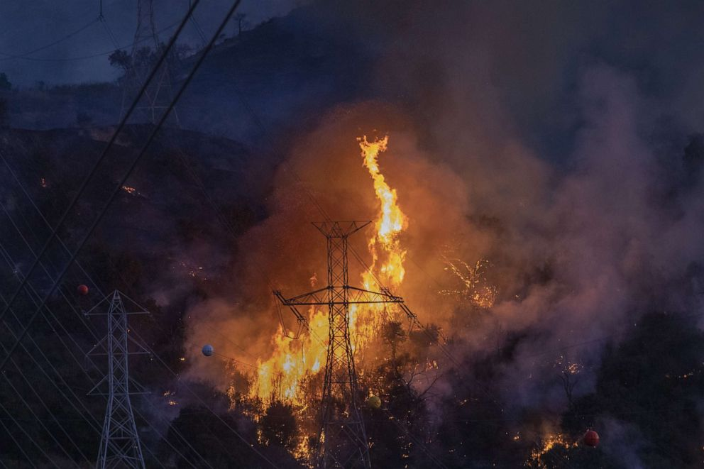 PHOTO: Flames heat up high power lines at the Saddleridge Fire on Oct. 11, 2019 near Newhall, Calif.
