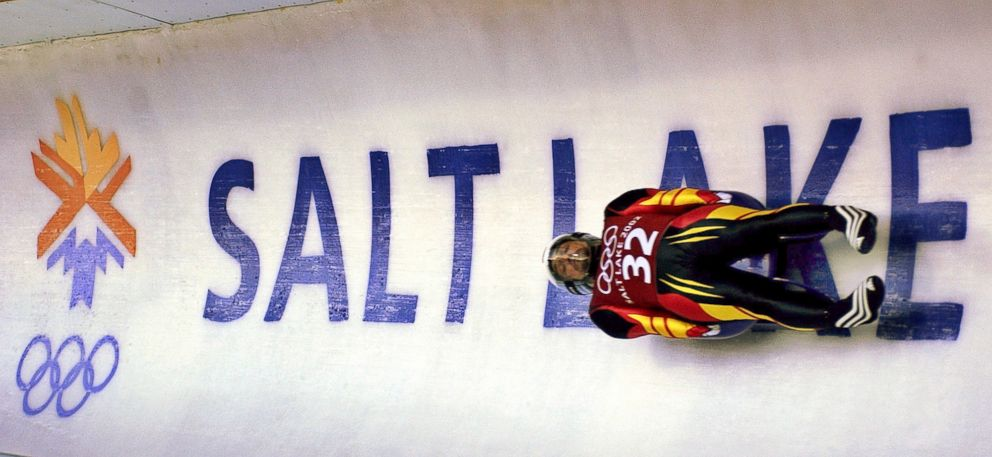 In this Feb. 9, 2002, file photo, Georg Hackl, of Germany, speeds past an Olympic logo during a practice run for the men's singles luge at the 2002 Salt Lake City Winter Olympics in Park City, Utah.