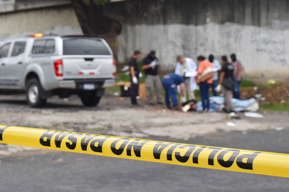 PHOTO: Salvadoran forensic police work at a crime scene, where a man was murdered, in San Salvador, May 29, 2019.