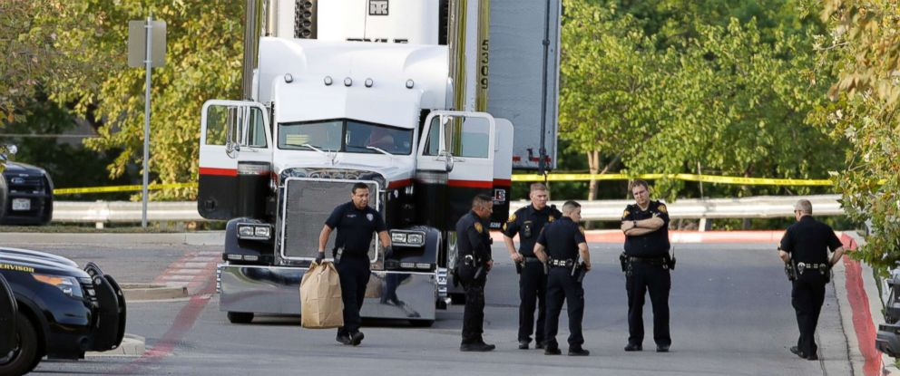PHOTO: San Antonio police officers investigate the scene, July 23, 2017, where eight people were found dead in a tractor-trailer loaded with at least 30 others outside a Walmart store in stifling summer heat, in San Antonio.