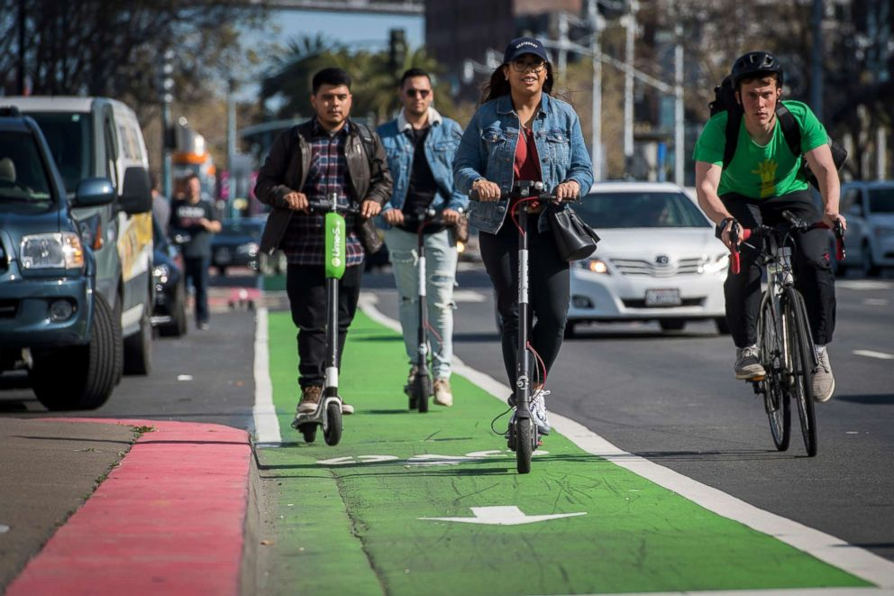 PHOTO: People ride electric scooters on the Embarcadero in San Francisco, April 13, 2018.