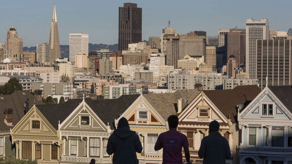 The silhouettes of pedestrians stand in front of Victorian homes and the downtown skyline in San Francisco, Dec. 29, 2015.