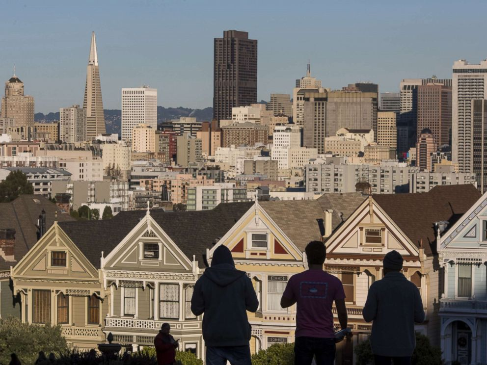 PHOTO: The silhouettes of pedestrians stand in front of Victorian homes and the downtown skyline in San Francisco, Dec. 29, 2015.