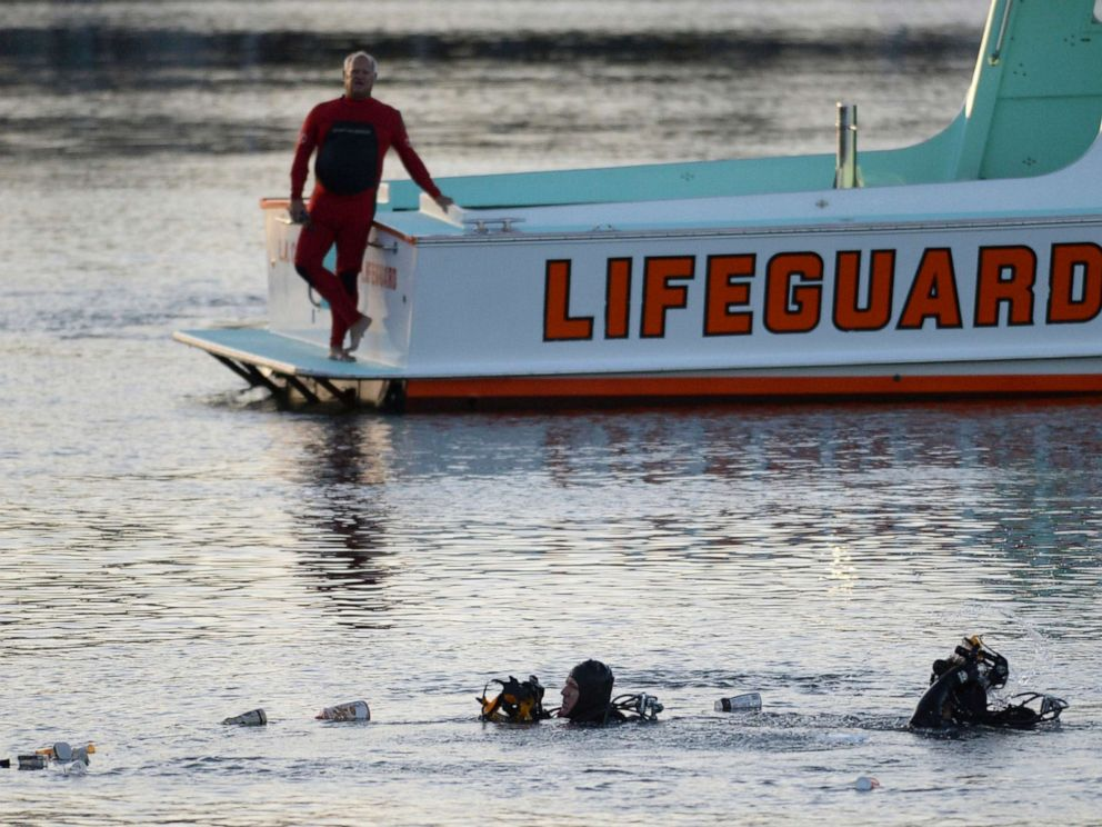 PHOTO: Divers emerge from the water as debris believed to be from a car floats to the surface, where a car went off a pier and into the water, in Los Angeles San Pedro harbor district, April 9, 2015.