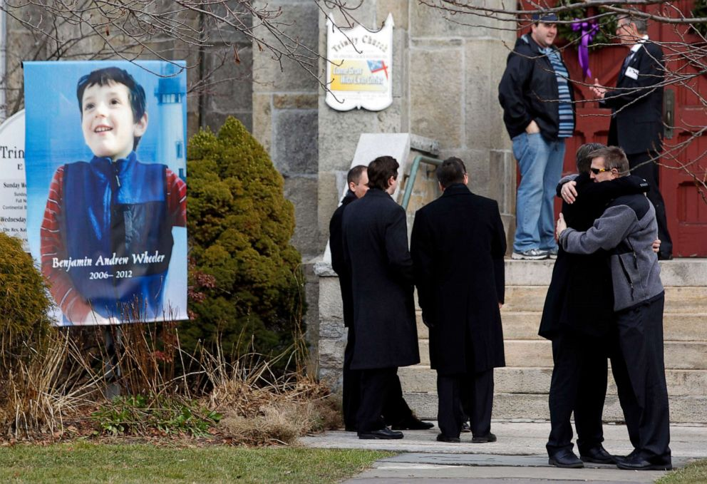 PHOTO: Mourners embrace outside of Trinity Episcopal Church while standing next to a portrait of Benjamin Andrew Wheeler, one of the students killed in the Sandy Hook Elementary School shooting, Dec. 20, 2012, in Newtown, Conn.