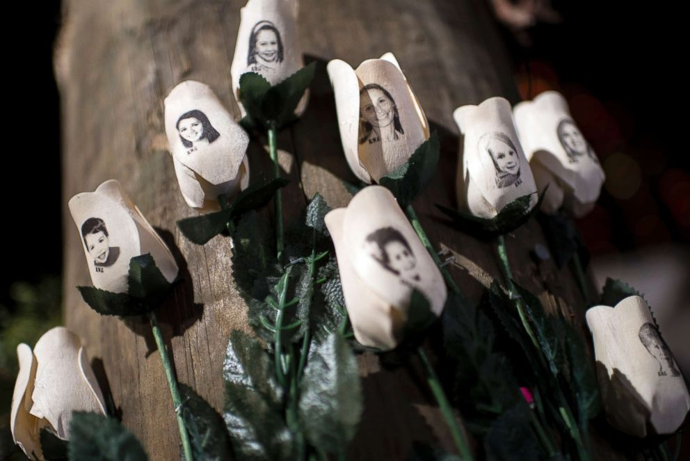 PHOTO: Pictures of victims of the Sandy Hook Elementary School shooting are seen on artificial roses at a roadside memorial, Dec. 20, 2012 in Newtown, Conn.