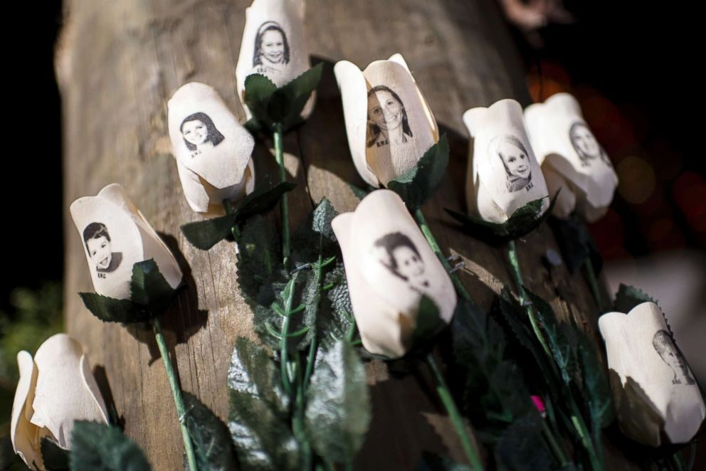 PHOTO: Pictures of victims of the Sandy Hook Elementary School shooting are seen on artificial roses at a roadside memorial on Dec. 20, 2012, in Newtown, Conn.