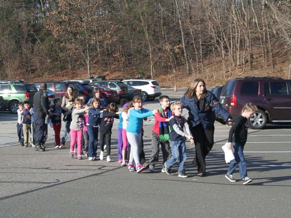 Two Connecticut State Police officers escort students and adults out of Sandy Hook Elementary School in Newtown, Conn., Dec. 14, 2012, after Adam Lanza, 20, entered the building and fatally shot 20 children and six adults before taking his own life.