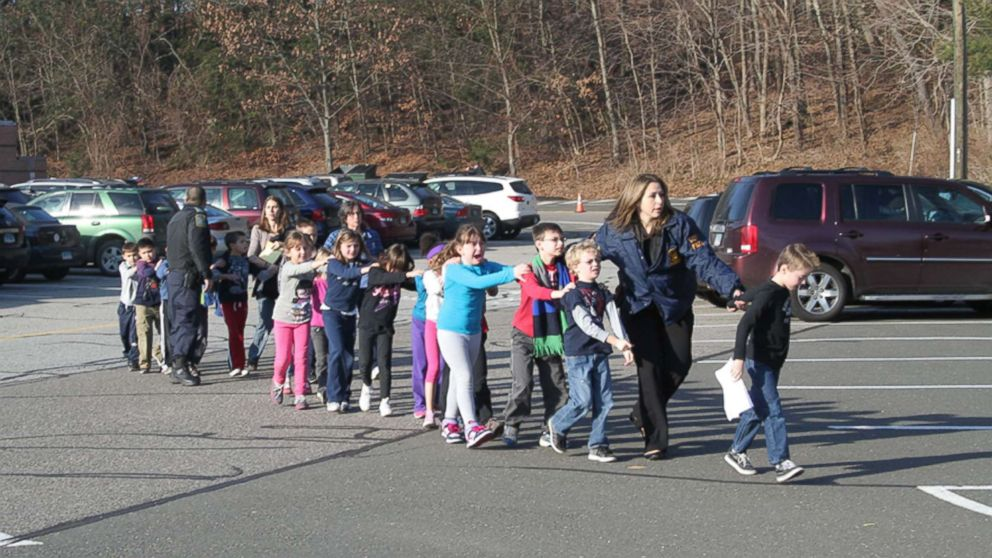 Two Connecticut State Police officers escort a class of students and two adults out of Sandy Hook Elementary School in Newtown, Conn., Dec. 14, 2012.