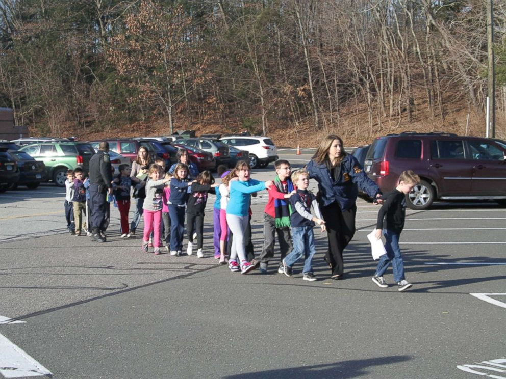 PHOTO: Two Connecticut State Police officers escort a class of students and two adults out of Sandy Hook Elementary School in Newtown, Conn., Dec. 14, 2012.