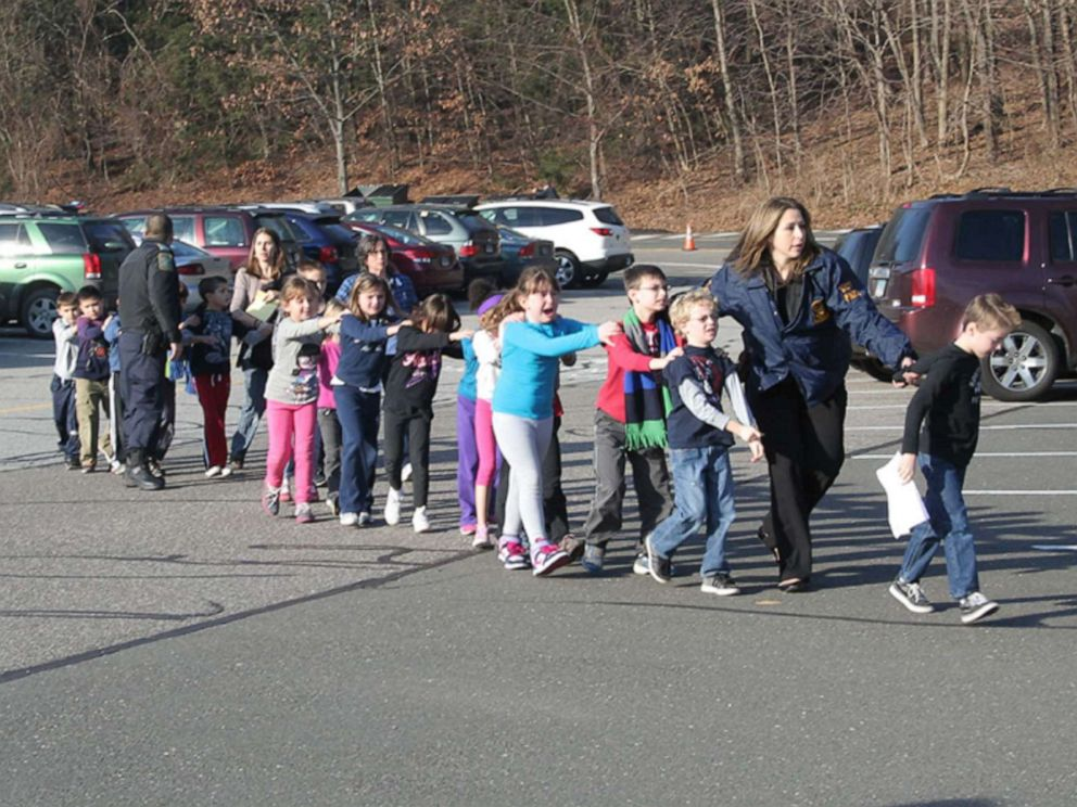 Two Connecticut State Police officers escort a class of students and two adults out of Sandy Hook Elementary School in Newtown, Conn., Dec. 14, 2012, after a shooter entered the building and killed 20 children and six adults before taking his own life.