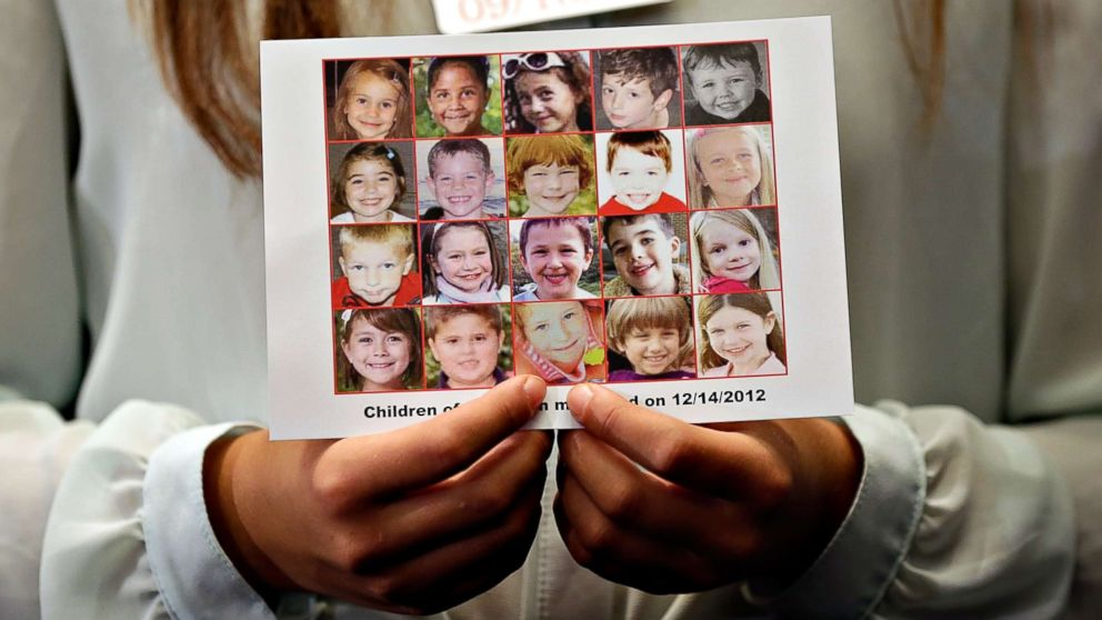 Kyra Murray holds a photo showing victims of the shooting at Sandy Hook Elementary School during a press conference at the U.S. Capitol calling for gun reform legislation, Sept. 18, 2013, in Washington, D.C.