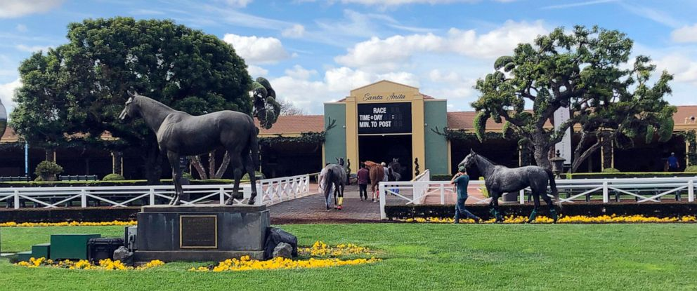 PHOTO: Horses are led to paddocks past the Seabiscuit statue during workouts at Santa Anita Park, in Arcadia, Calif., Thursday, March 28, 2019.