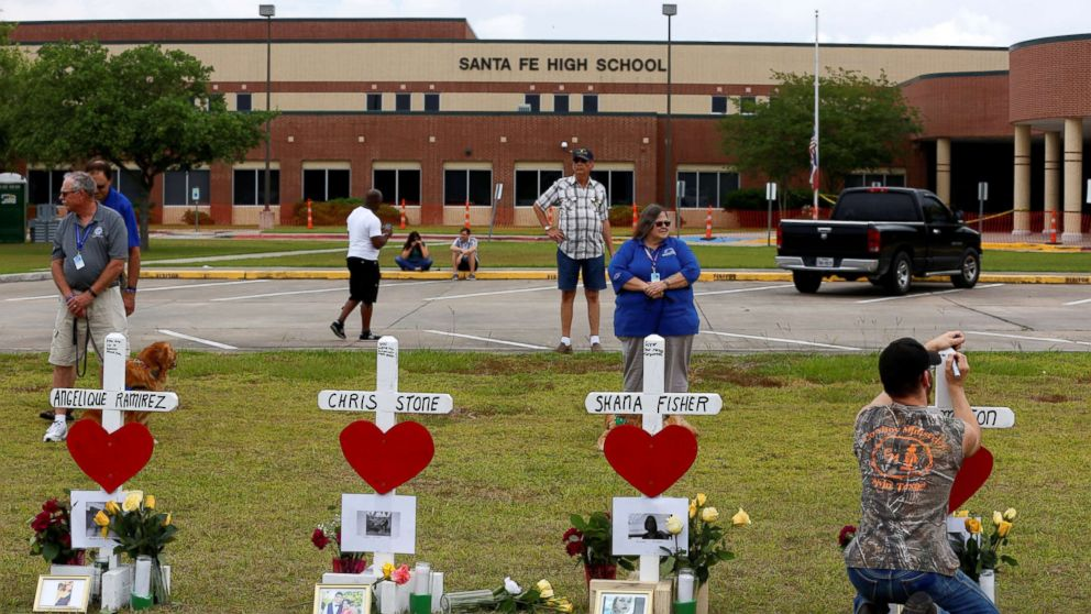 People gather at a makeshift memorial left in memory of the victims killed in a shooting at Santa Fe High School in Santa Fe, Texas, May 21, 2018.