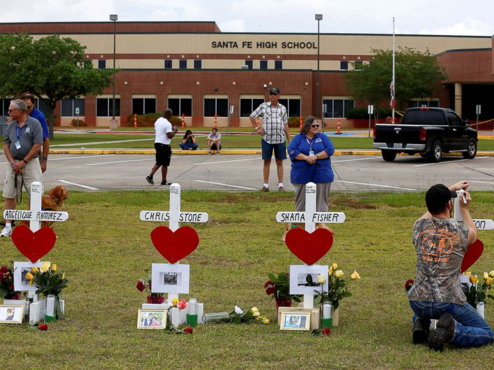 PHOTO: People gather at a makeshift memorial left in memory of the victims killed in a shooting at Santa Fe High School in Santa Fe, Texas, May 21, 2018.