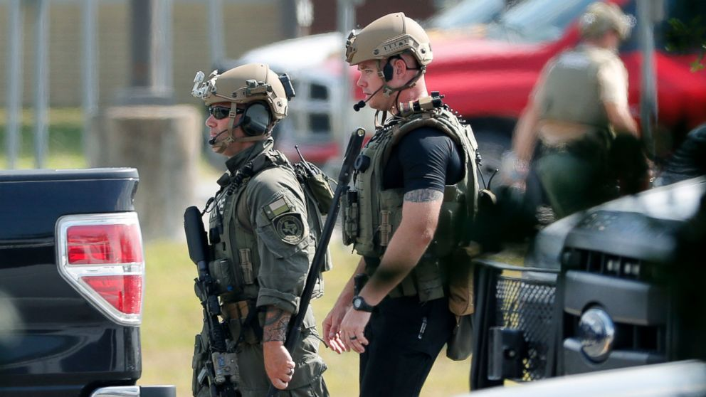 Police officers in tactical gear move through the scene at Santa Fe High School after a shooting on May 18, 2018, in Santa Fe, Texas.