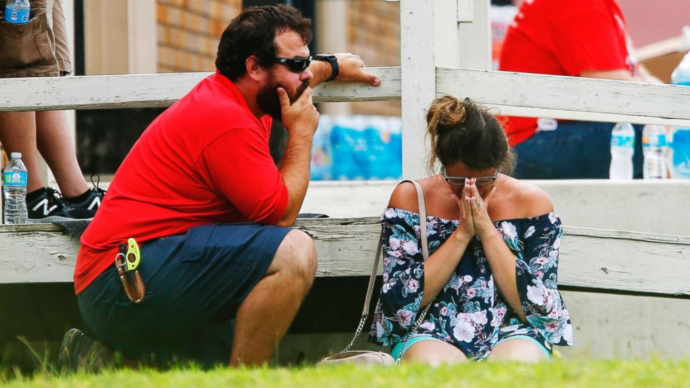 A woman prays in the grass outside the Alamo Gym where parents wait to reunite with their kids following a shooting at Santa Fe High School, May 18, 2018, in Santa Fe, Texas.
