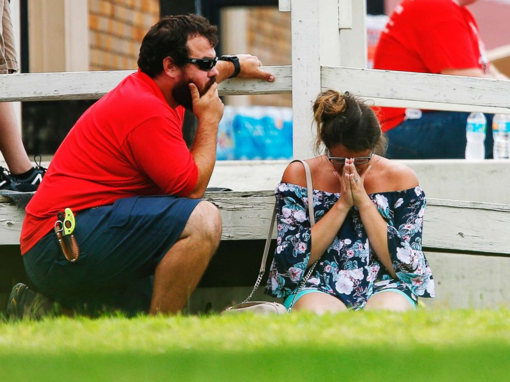 PHOTO: A woman prays in the grass outside the Alamo Gym where parents wait to reunite with their kids following a shooting at Santa Fe High School, May 18, 2018, in Santa Fe, Texas.