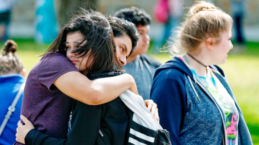 Santa Fe High School freshman Caitlyn Girouard, center, hugs her friend outside the Alamo Gym where students and parents wait to reunite following a shooting at Santa Fe High School, May 18, 2018, in Santa Fe, Texas.