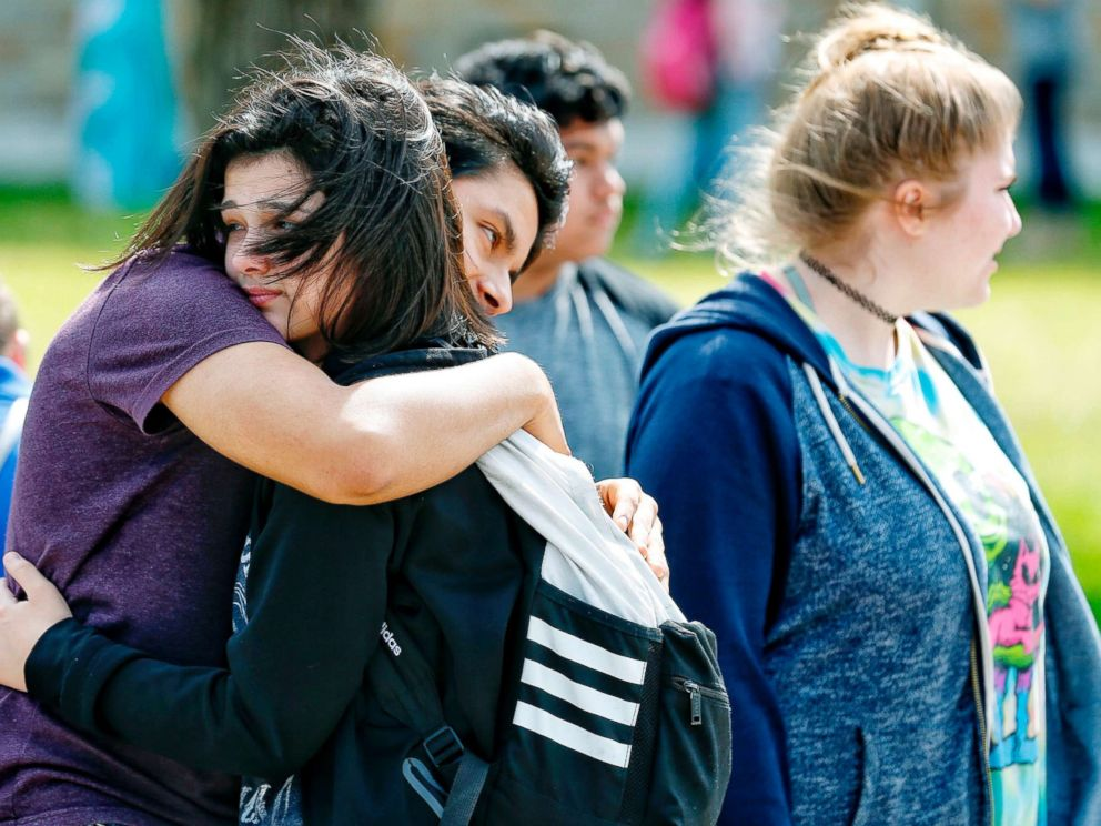 PHOTO: Santa Fe High School freshman Caitlyn Girouard, center, hugs her friend outside the Alamo Gym where students and parents wait to reunite following a shooting at Santa Fe High School, May 18, 2018, in Santa Fe, Texas.
